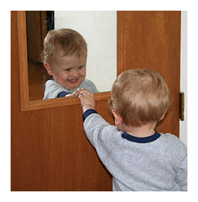Child looking at self in mirror
